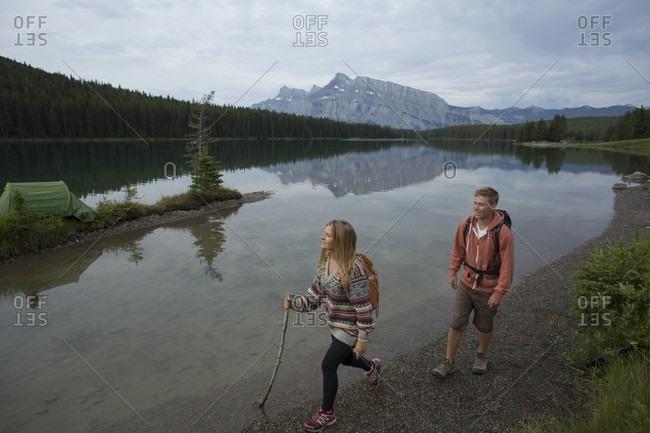 Young couple hikes along mountain lake