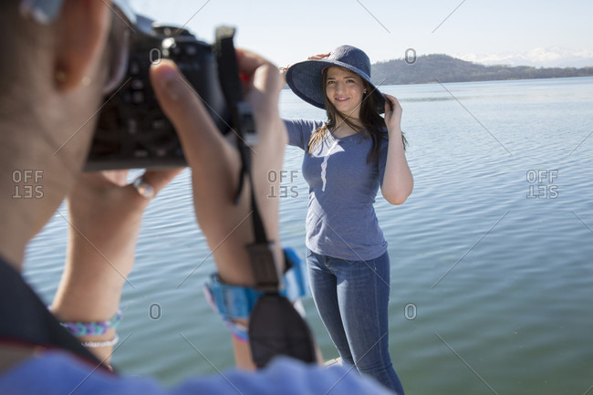 POV of teen girl taking photo of friend in hat