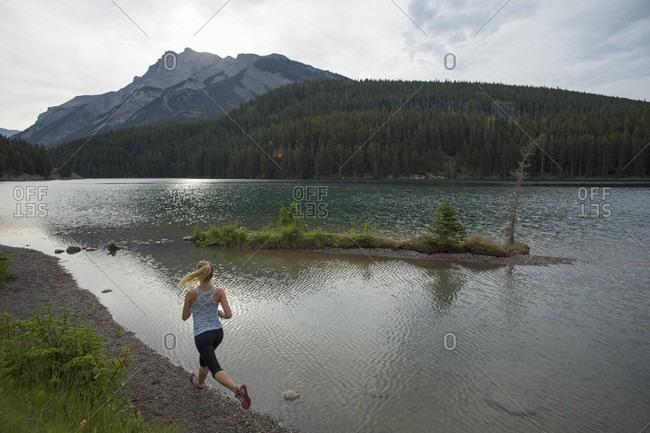 Young woman runs along edge of mountain lake