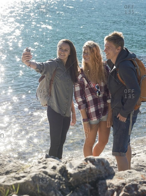 Group of teen hikers take pic with smartphone, mountain lake