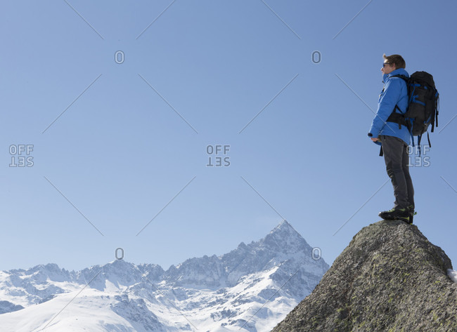 Portrait of mountaineer on summit, above mountains