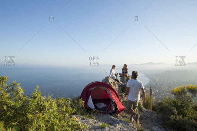 Family with tent on hillside above sea