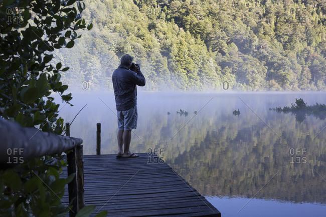 Mature man takes photo on dock in lake at sunrise