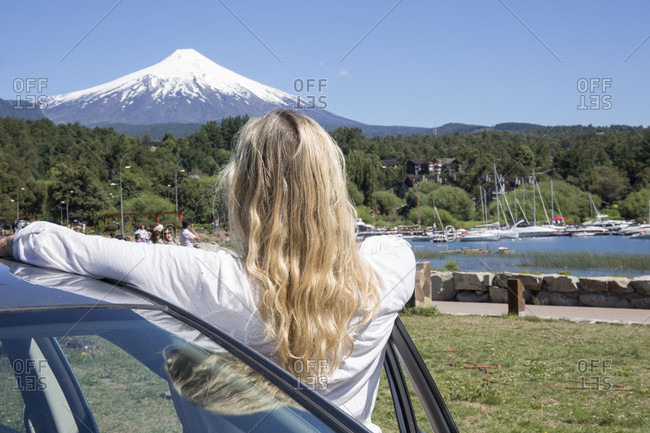 Woman leans against car and looks at snow capped volcano