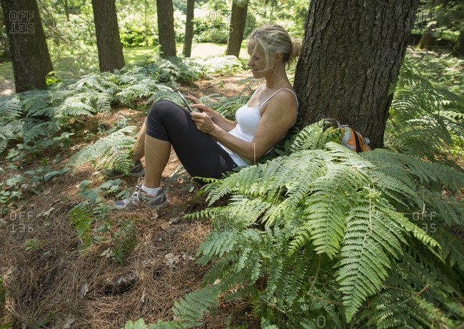 Woman relaxes in forest, uses digital tablet