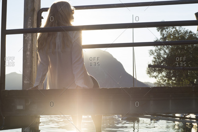 Woman relaxes on wooden pier, looks across lake