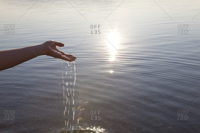 Water pours from hands into tranquil lake
