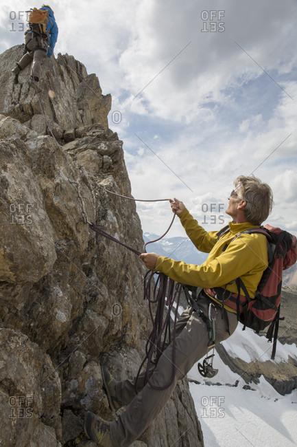 Mountaineer belays teammate on summit ridge