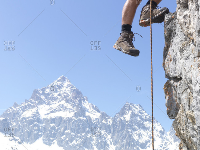 Mountaineer's legs ascend mountain ridge