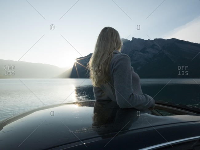 Woman looks out from car, mountain lake