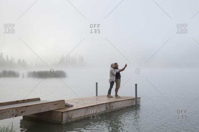 Couple take selfie pic across mountain lake, fog