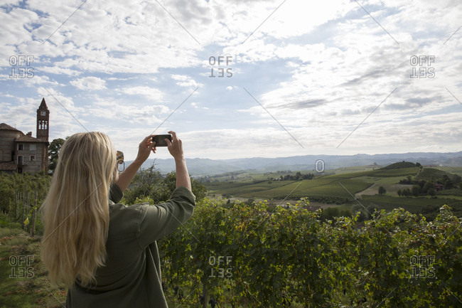 Woman takes pic across hills and vineyards