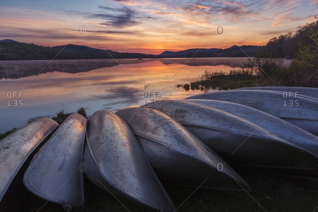 Stack Of Aluminum Canoes At The Edge Of Indian Lake In Adirondack Mountains