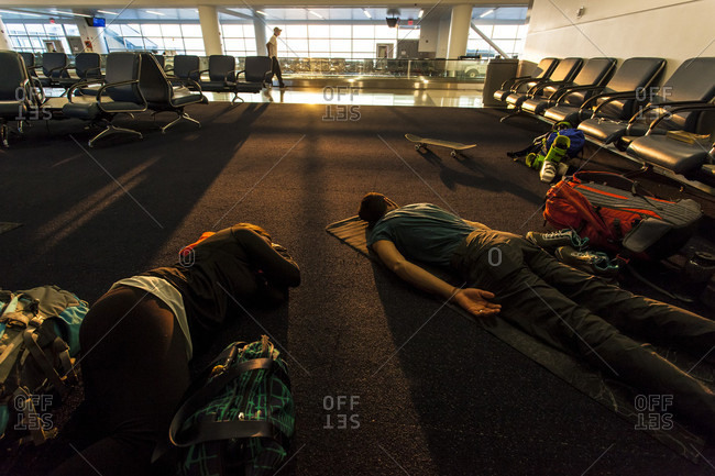 Two Travelers Who Just Took An Overnight Flight Sleeping On The Airport Floor
