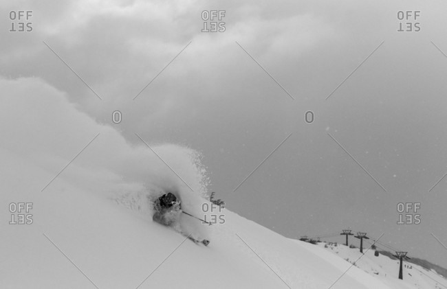 A Skier Makes A Turn In Deep Powder Snow And Nearly Covers Himself With Blowing Snow On A Stormy Day In Bounds At Cerro Catedral In Argentina