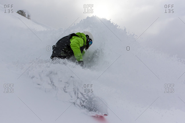 A Female Snowboarder Makes A Turn In Deep Powder Snow And Nearly Covers Herself With Blowing Snow On A Stormy Day In Bounds At Cerro Catedral In Argentina.