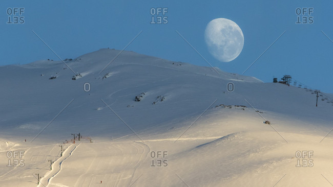 A Nearly Full Moon Is Just About To Set Below The Ridge Line As The Sun Rises At Cerro Catedral