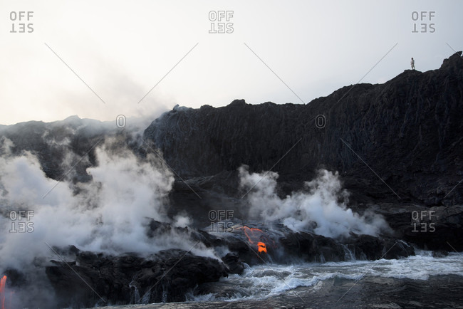 A Hiker Pauses On The Edge Of The Kalapana Lava That Has Been Flowing Into The Ocean