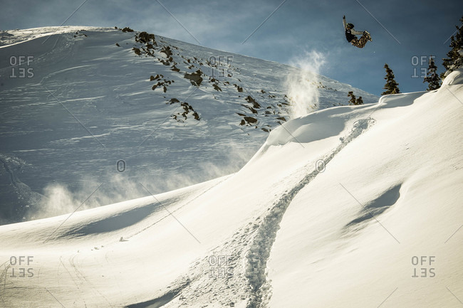 Snowboarder Jumping Off A Natural Hip In The Colorado Backcountry