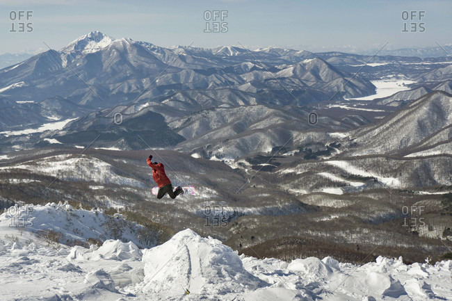 A Snowboarder Does A Method In The Backcountry With Amazing Japanese Mountain Backdrop