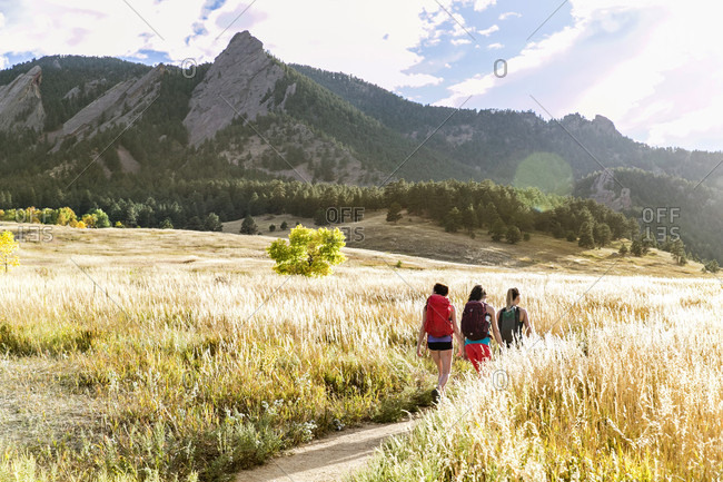 A Female Hikers Walk On A Trail Beneath The Flatirons In Colorado