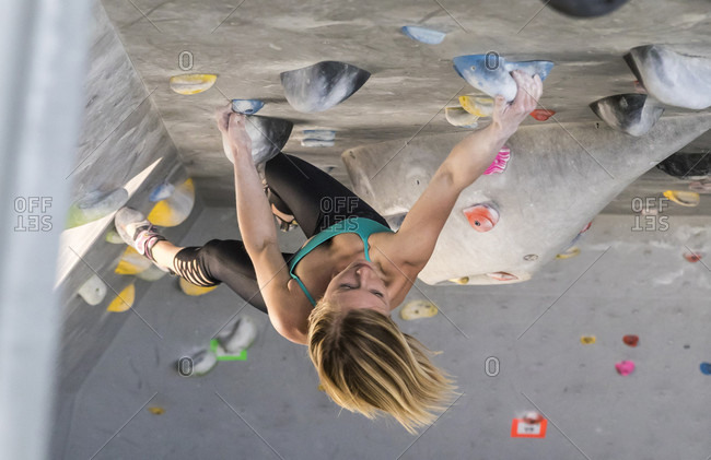 A Young Female Climber On An Overhanging Roof In A Climbing Gym