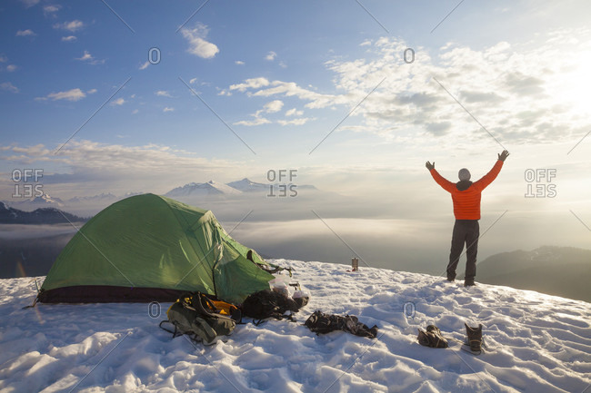 A Camper Lifts His Hand In The Air As He Watches The Sunrise From His Campsite On A Snow Covered Mountain