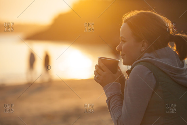 A Woman Enjoying A Hot Drink At A Beach Near Tofino, British Columbia, Canada