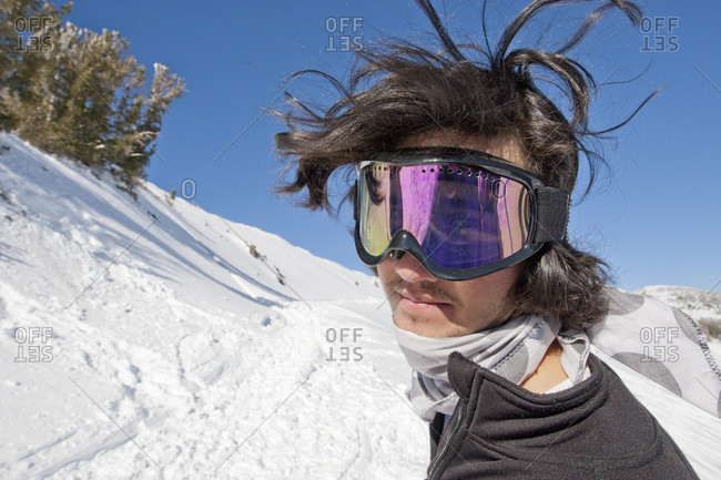 Young male snowboarder with wild hair caught in a candid moment.