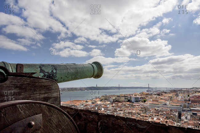 A Cannon At The Castle Of Sao Jorge With The City In Background At Lisbon, Portugal