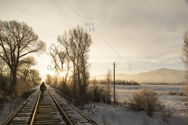 Person Walking The Railroad Track On The Way To Fly Fishing On The Provo River In Utah At Sunrise
