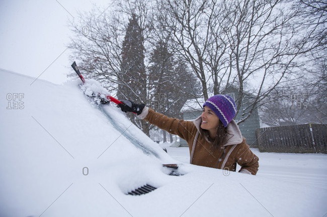 An Adult Woman Clearing Off Her Windshield After A Fresh Blanket Of Snowfall