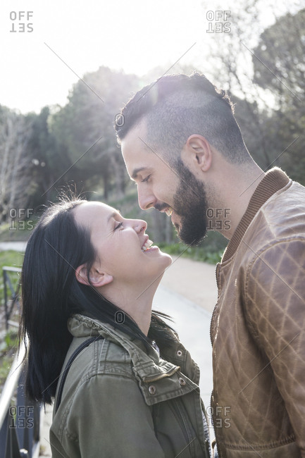 Couple smiling and having fun in loving attitude in a park in Madrid, Spain