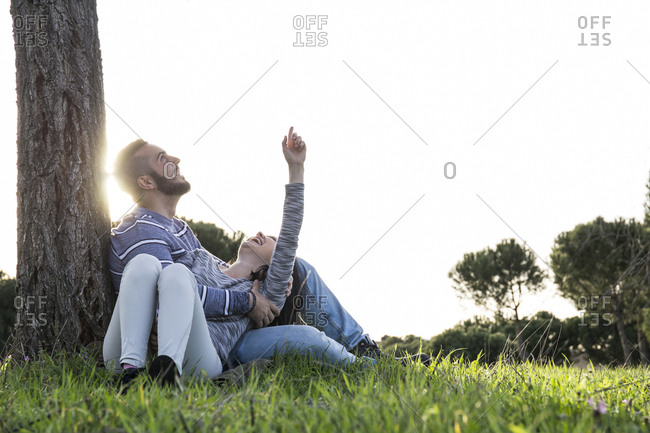 Couple in loving attitude pointing up leaning on a tree sitting in the grass in Madrid, Spain