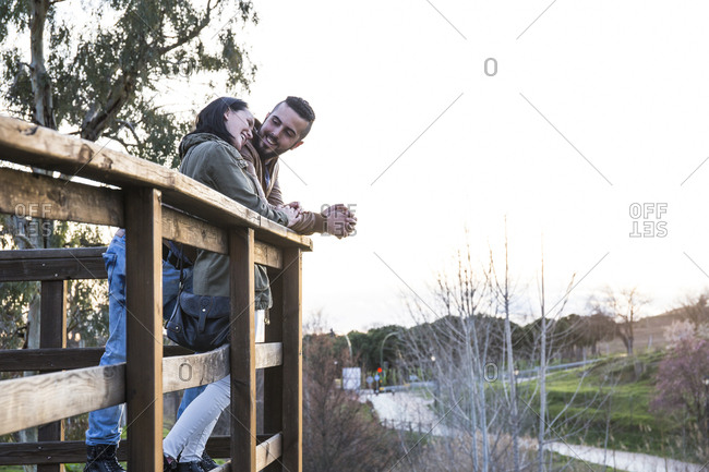 Couple talking in loving attitude leaning on a wooden railing in Madrid, Spain