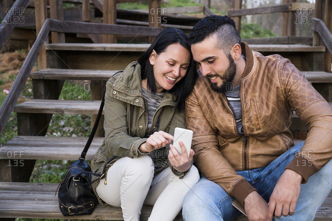 Couple smiling and having fun sitting on wooden stairs using a phone in Madrid, Spain
