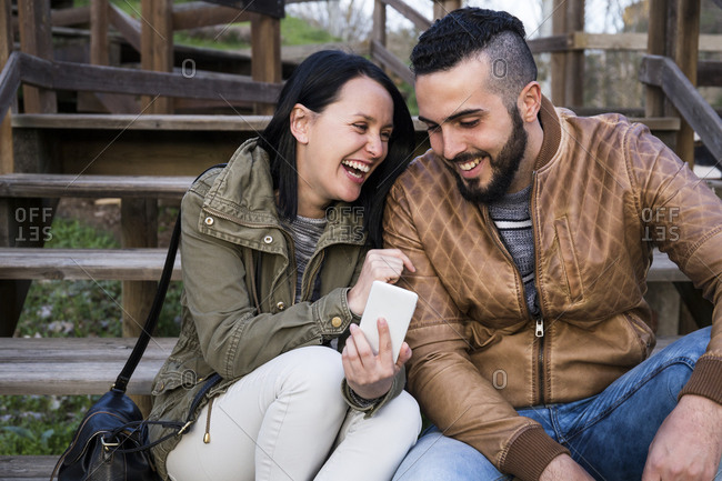 Couple smiling and laughing while sitting on wooden stairs using a phone in Madrid, Spain
