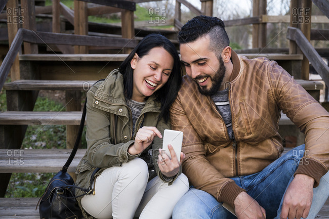 Couple laughing while sitting on wooden stairs using a phone in Madrid, Spain