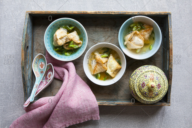 Chicken wonton soup bowls on a wooden tray