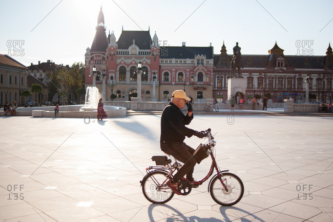 Oradea, Romania - July 22, 2015: Man riding bike in the city center of Oradea, Romania