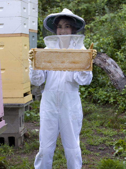Young apiarist working bee hives in Upper Saddle River, New Jersey
