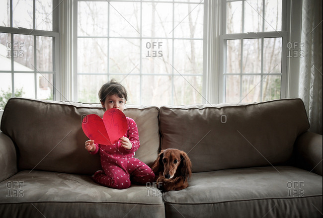 Little girl and dog sit on couch while holding a paper heart