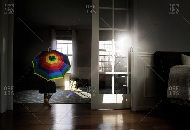 Girl running indoors with umbrella