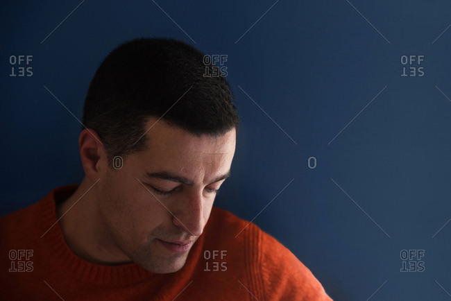 Portrait of a man looking down against blue background
