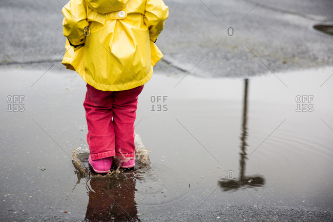 Girl in yellow raincoat jumping in a rain puddle
