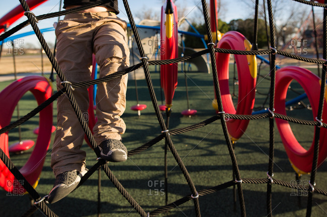 Child climbing on ropes on a playground