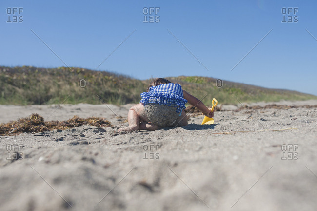 Baby playing in beach sand