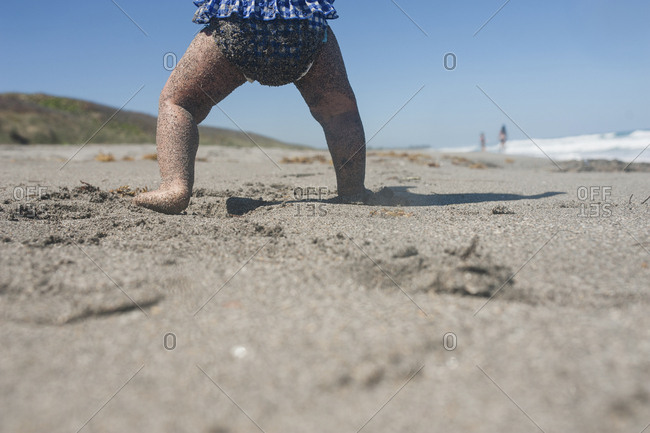 Close-up of chubby baby legs covered in sand