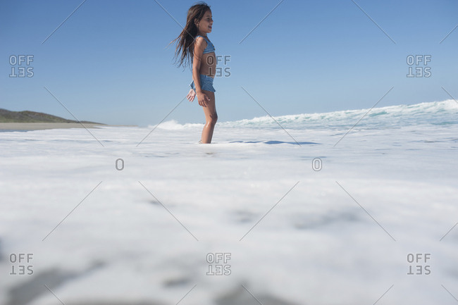Girl standing ankle deep in the ocean
