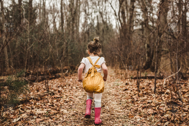 Girl running away in a wooded setting